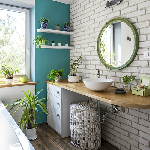 Teal wall bathroom with green accent mirror